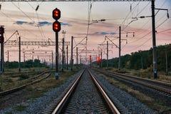 Resa med tåg trafikljus och infrastruktur under härlig solnedgång, färgrik himmel, trans. och industriellt begrepp Royaltyfri Foto