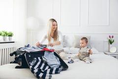 Resa med ungar Lycklig moder med hennes barnemballagekläder för ferie royaltyfri foto