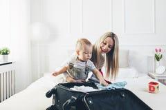 Resa med ungar Lycklig moder med hennes barnemballagekläder för ferie royaltyfri fotografi