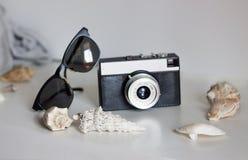 Resa på semester, en tappningkamera och solglasögon royaltyfri bild