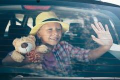 Resa turism - flicka med nallebjörnen som är klar för loppet för sommarsemester Barn som går på affärsföretag Billopp arkivfoton