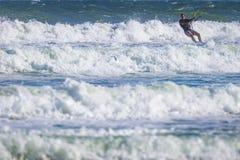 Resaca atletic joven de la cometa del montar a caballo del hombre en un mar Foto de archivo