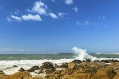 Resaca del océano, cielo azul y chapoteo sobre las piedras Naturaleza imágenes de archivo libres de regalías