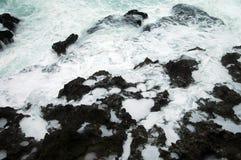 Resaca en piedras negras Foto de archivo libre de regalías