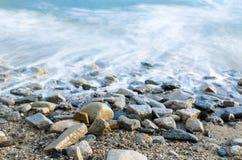 Resaca que se rompe sobre los guijarros de la playa - exposición larga del océano imagenes de archivo