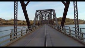 Resande över metallvägbron som spänner över floden arkivfilmer