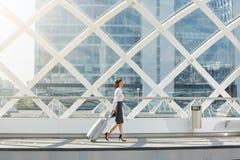Resande affärskvinna som går med resväskan i terminal royaltyfri bild