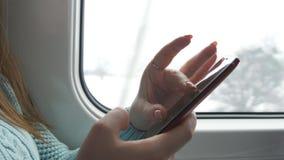 Resande för ung kvinna i ett drev och en användamobiltelefon Den kvinnliga handen överför ett meddelande från smartphonen Arm av  stock video