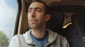 Resande för ung man på ett drev och blickar ut fönstret