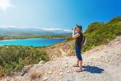Resande flicka som håller ögonen på med kikare på havsbakgrunden Royaltyfria Foton