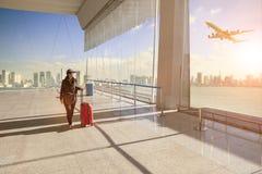 Resande kvinna med att höra hemma bagage som går i flygplatstermin arkivbild