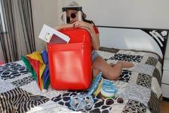 Resande kvinna med resväskan på säng i hotell Royaltyfria Foton