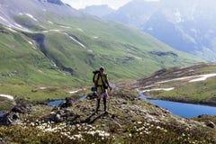 Resande man på en bakgrund av alpina ängar med en sjö Arkivfoto