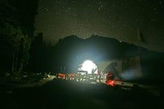 Resande sammanträde i en stjärnklar natt i bergen Arkivbild