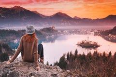 Resande ung kvinna som ser på solnedgång på Bled sjön, Slovenien, Royaltyfri Fotografi