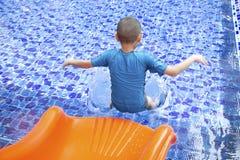 Resbalador asiático de la piscina del juego del muchacho Imagenes de archivo