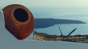 Resbalador tirado ofreciendo una urna tradicional de Cycladic, y barco viejo y el mar Mediterráneo egeo almacen de metraje de vídeo