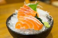 Resbale el sashimi de color salmón en el hielo en cuenco negro fotos de archivo libres de regalías