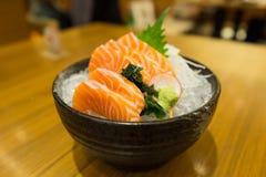 Resbale el sashimi de color salmón en el hielo en cuenco negro imágenes de archivo libres de regalías