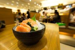 Resbale el sashimi de color salmón en el hielo en cuenco negro foto de archivo libre de regalías