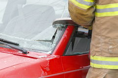 Rescue # 1. Fireman cutting into a wrecked car to remove the driver Stock Photography
