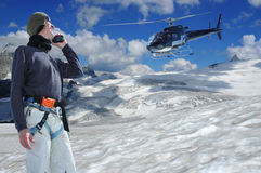 Rescue. Radioing for help on a walkie-talkie from a helicopter on a high glacier with the matterhorn in the background. the mountain guide is equiped with Royalty Free Stock Photography