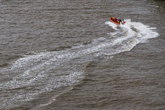 Rescue boat. River rescue boat in orange with full crew Stock Photography
