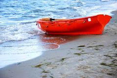 Rescue boat. Small red rescue boat on a beach, prepared to save people's lifes royalty free stock photography