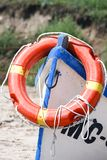 Rescue boat with lifebuoy. Red lifebuoy with yellow stripes placed on a wooden rescue boat Royalty Free Stock Photography