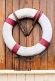 Rescue buoy. White rescue buoy hanging on wooden wall of a boat Royalty Free Stock Photography