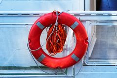 The rescue circle hangs aboard the yacht, a red circle with ropes to save the drowning man royalty free stock image