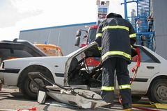 Rescue firefighter in action for saving people from a car crash in front of other people in Sofia, Bulgaria - Sep,11, 2007. stock image