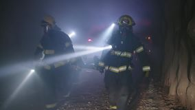 Rescue forces search for survivers inside a dark tunnel using flashlights
