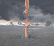 Rescue. Hand of drowning man in a small puddle of water and helping hand Royalty Free Stock Photos