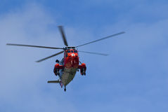 Rescue helicopter. A rescue helicopter flying over the coast of Cornwall stock image