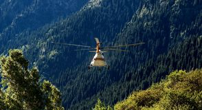 Rescue helicopter flies away in mountains Royalty Free Stock Image