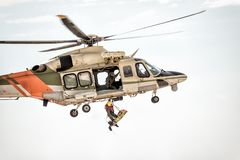 Rescue helicopter in flight winching rescuer royalty free stock photos