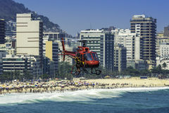 Rescue helicopter flying over crowded Copacabana Beach during hot summer day in Rio de Janeiro, Brazil. Royalty Free Stock Image