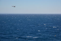 Rescue helicopter flying over the sea Stock Photos