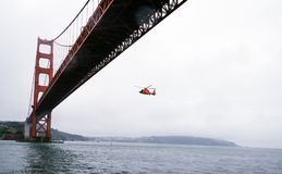 Rescue Helicopter Flying Under Golden Gate Bridge Royalty Free Stock Photography
