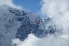 Rescue helicopter over big clouds, Gorak Shep, Everest Base Camp trek, Nepal royalty free stock photography