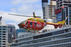 Rescue helicopter over the city. Auckland, New Zealand. The Westpac rescue helicopter, a MBB/Kawasaki BK 117, flying over Auckland harbor. In the background is a stock images