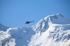 Rescue helicopter over a mountain ridge Stock Images
