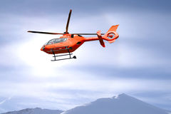 Rescue helicopter over mountain summits Stock Photo