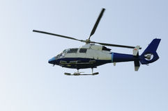 Rescue helicopter rescuing. Blue rescue helicopter flying with blue sky background stock image