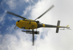Rescue Helicopter. Helicopter is rescuying in the Mountains with a cable stock photography