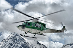 Rescue helicopter in the sky. Above the Alps Stock Photography