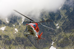 Rescue helicopter taking off in cloudy Tetra mountains in Slovak royalty free stock images
