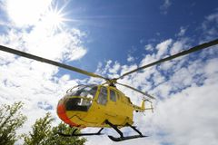 Rescue helicopter. Yellow medical rescue helicopter flying above trees royalty free stock image