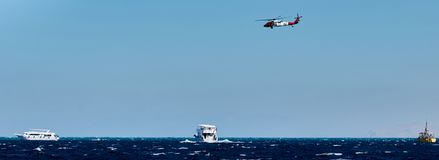 Rescue helihopter helping take off. Look from yacht on helping helihopter which helping humans Stock Image